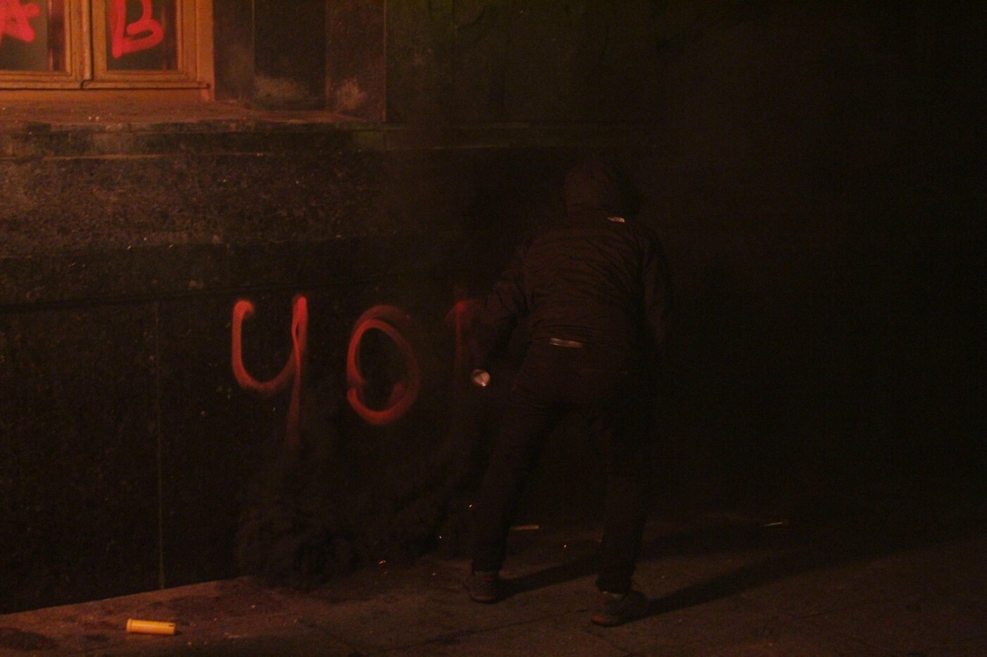 Активист разрисовывает фасад здания, Фото: 44.ua