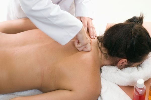 девушке делают массаж шеи